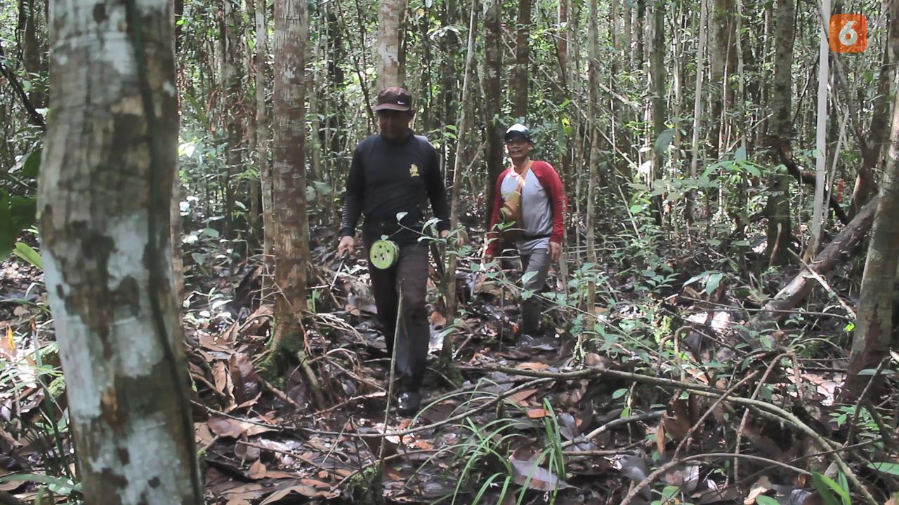 Anton Suparto (kanan) bersama rekannya David saat berpatroli di Hutan Desa Genting Tanah, Kabupaten Kutai Kartanegara.