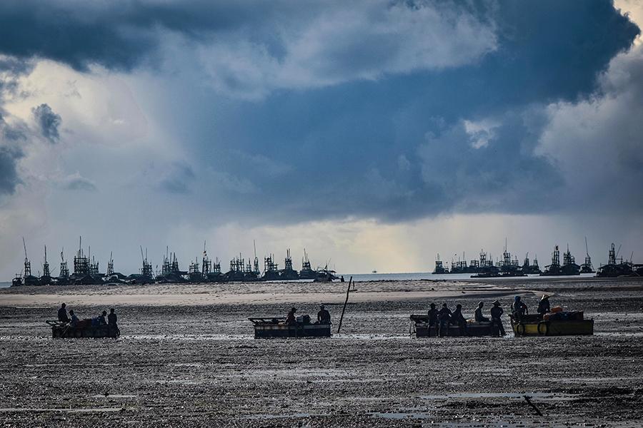 Sejumlah nelayan pulang dari melaut dan harus melewati hamparan lumpur di sekitar Pesisir Desa Batu Belubang yang sudah kehilangan mangrovenya. Foto: Nopri Ismi/Mongabay Indonesia